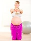 Lächelnde schwangere Frau, die Eignungübungen tut Stockfotografie