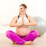 Lächelnde schwangere Frau, die Yogaübungen tut Stockfotos