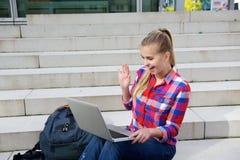 Lächelnde sitzende Außenseite des Studenten, die zum Laptop wellenartig bewegt Lizenzfreie Stockfotos