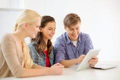 Lächelnde Studenten mit Tabletten-PC-Computer in der Schule Lizenzfreie Stockfotografie