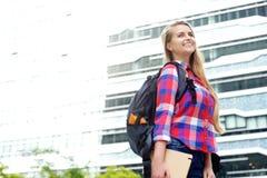 Lächelnde Studentin, die draußen mit Tasche und Buch geht Lizenzfreies Stockbild