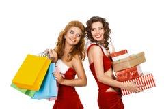 Lächelnde Weihnachtsfrauen, die Geschenk und bunte Pakete halten Stockbild