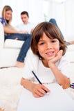 Lächelnde Zeichnung des kleinen Jungen, die auf Fußboden liegt Stockfotografie