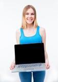 Lächelnde zufällige Frau, die Laptopschirm zeigt Stockfotos