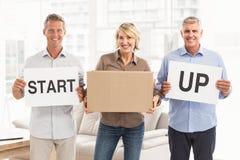 Lächelnde zufällige Geschäftsleute Halten beginnen oben Zeichen Stockbild