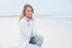 Lächelnde zufällige junge Frau, die am Strand sich entspannt Stockbild