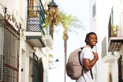 Lächelnder afrikanischer Reisemann mit Tasche hörend Musik Stockfoto