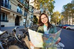 Lächelnder asiatischer weiblicher Tourist mit Karte von Paris Stockfotografie