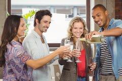 Lächelnder auslaufender Champagner des Geschäftsmannes im Glas Stockfotografie