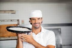 Lächelnder Bäcker Holding Dough Tray At Bakery Lizenzfreies Stockfoto