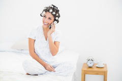 Lächelnder Brunette in den Haarrollen am Telefon auf Bett Stockbild