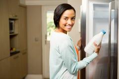 Lächelnder Brunette, der Milchflasche mit offenem Kühlschrank hält Stockbild