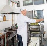 Lächelnder Chef Processing Pasta Sheet in der Maschinerie Lizenzfreie Stockbilder