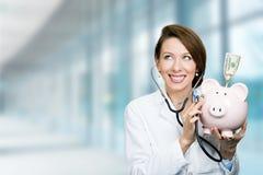 Lächelnder Doktor, der das Hören auf Sparschwein mit Stethoskop hält Stockbilder