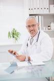 Lächelnder Doktor, der einen Tabletten-PC verwendet Stockfotografie