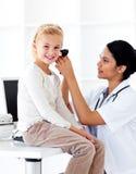 Lächelnder Doktor, der ihren Patienten \ 's-Ohren überprüft Stockfotografie
