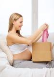Lächelnder Öffnungspaketkasten der schwangeren Frau Lizenzfreies Stockfoto