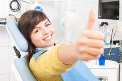 Lächelnder Frauenpatient, der wie in Zahnarztbüro zeigt Stockfotografie