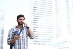 Lächelnder gestikulierender Mann bei der Anwendung des Handys in der Stadt Lizenzfreies Stockfoto