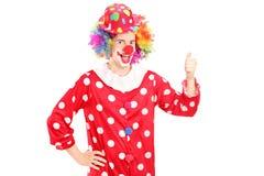 Lächelnder glücklicher Clown im roten Kostüm, das Daumen aufgibt Lizenzfreies Stockbild