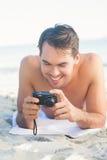 Lächelnder gutaussehender Mann, der auf seinem Tuch betrachtet seine Kamera liegt Stockbild