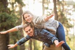 Lächelnder gutaussehender Mann, der piggyback seiner Freundin gibt Lizenzfreie Stockfotos