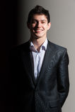 Lächelnder hübscher Geschäftsmann in der Klage auf grauem Hintergrund Stockbilder
