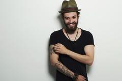 Lächelnder Hippie-Junge Gut aussehender Mann im Hut Grober bärtiger Junge mit Tätowierung Stockfoto
