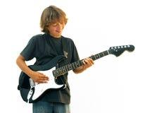 Lächelnder jugendlich Junge, der Gitarre spielt Lizenzfreie Stockfotos