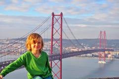 Lächelnder Junge beim Golgen versehen Brücke, Lissabon mit einem Gatter Lizenzfreie Stockfotos