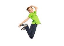 Lächelnder Junge, der in einer Luft springt Stockfotografie