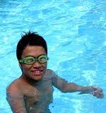 Lächelnder Junge in einem Swimmingpool Stockbilder