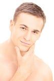 Lächelnder junger hemdloser Mann, der nachdem dem Rasieren aufwirft Stockfotografie