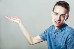 Lächelnder junger Mann, der etwas darstellt Lizenzfreie Stockfotos