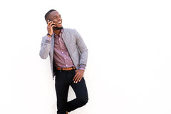 Lächelnder junger Mann, der am Handy gegen weißen Hintergrund spricht Lizenzfreie Stockfotos