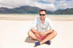 Lächelnder junger Mann mit der Sonnenbrille, die auf einem Strand sitzt Stockfotos