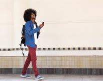 Lächelnder junger schwarzer Mann, der mit Tasche und Handy geht Lizenzfreies Stockfoto