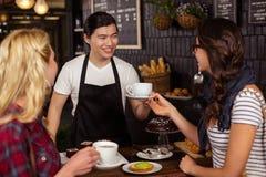 Lächelnder Kellner, der einem Kunden einen Kaffee dient Stockfotografie