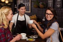 Lächelnder Kellner, der einem Kunden einen Kaffee dient Stockfoto