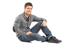 Lächelnder Kerl, der auf einem Boden und dem Betrachten der Kamera sitzt Stockbilder