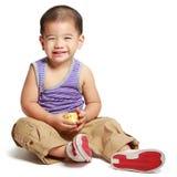Lächelnder kleiner asiatischer Junge, der auf Boden sitzt Stockfoto