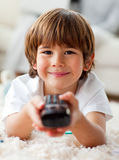 Lächelnder kleiner Junge, der Fernsieht, auf dem Fußboden zu liegen Stockbilder