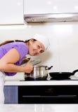 Lächelnder Koch, der über einen Topf auf dem Ofen verbiegt Lizenzfreie Stockfotografie