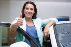 Lächelnder Kunde, der auf Auto bei Daumen aufgeben sich lehnt Lizenzfreie Stockfotos