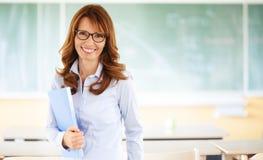 Lächelnder Lehrer, der im Klassenzimmer steht Stockfotos