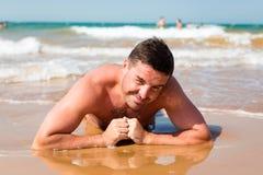 Lächelnder Mann, der auf dem Strand auf Seehintergrund liegt Stockfotos