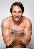 Lächelnder Mann, der sein gesundes Gesicht mit Wasser wäscht Stockfotografie