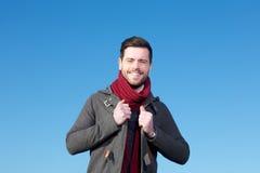 Lächelnder Mann in der Winterjacke, die gegen blauen Himmel aufwirft Stockfotografie