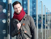 Lächelnder Mann mit der Jacke und Schal, die sich draußen entspannen Stockbild