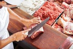 Lächelnder Metzger-Cutting Meat At-Zähler Stockbild